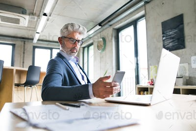 Mature businessman with laptop and smart phone.
