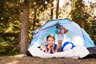 Beautiful little girls in tent camping by the lake.
