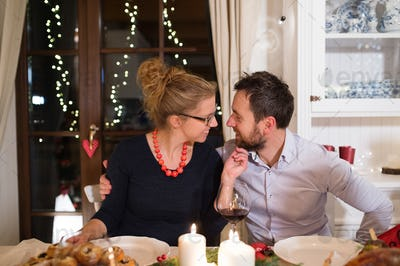 Young couple celebrating Christmas together at home.