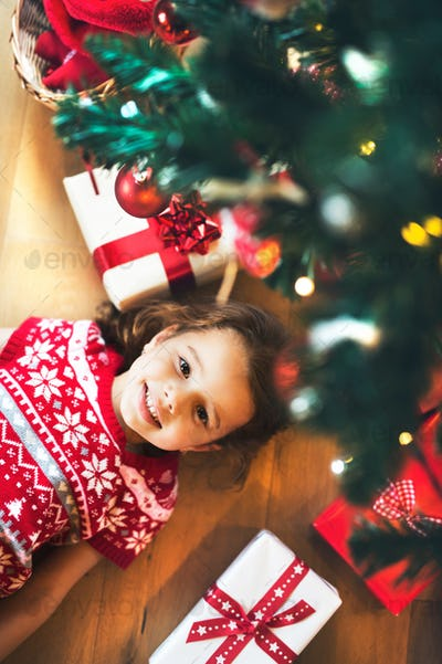 Little girl lying under Christmas tree among presents,
