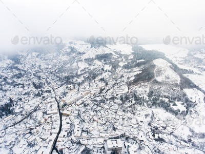 Aerial view of small town with hills in winter.