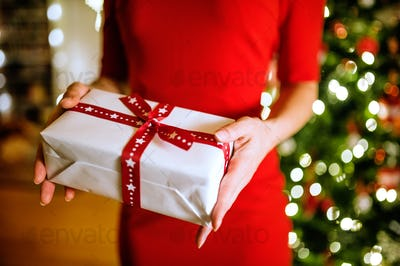 Unrecognizable woman in front of Christmas tree holding present