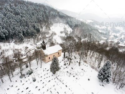 Aerial view of a church and a cemetery.