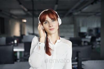 Businesswoman with big earphones in her office.