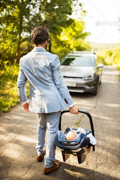 Young father with his little baby going into the car.