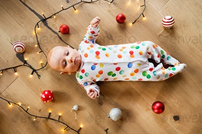 Little baby boy on the floor at Christmas time.
