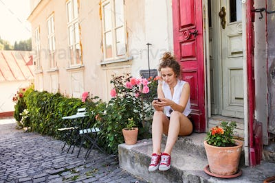 Young woman with a smartphone at the doorstep.