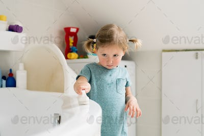 Little girl in bathroom cleaning bathtub with a brush.