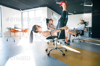 Business woman riding a chair and racing in the workplace.