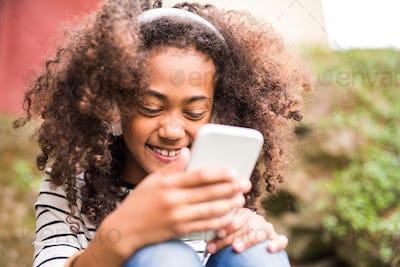 Beautiful african american girl with smart phone and earphones.