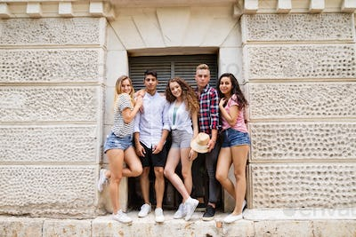 Attractive teenage students posing in front of university.