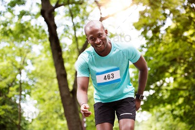 Young fit afro-american man running in park.