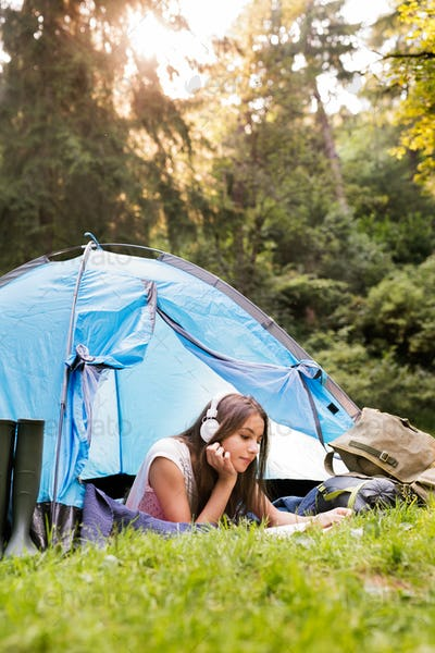 Teenage girl in front of tent camping in forest.