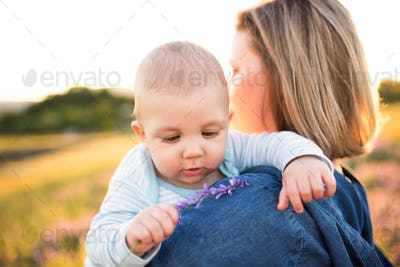 Unrecognizable mother in nature with baby son in the arms.