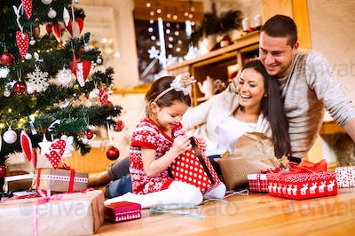 Young family with daughter at Christmas tree at home.