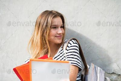 Beautiful teenage student posing in front of university.