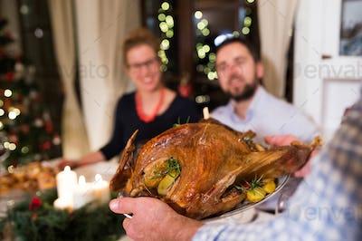 Family celebrating Christmas. Roasted turkey on tray.