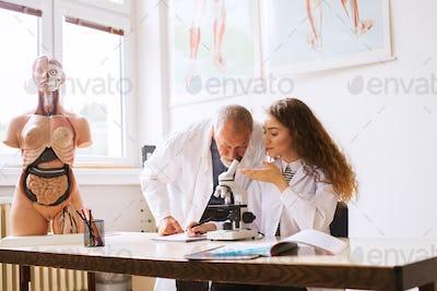 Senior teacher teaching biology to student in laboratory.