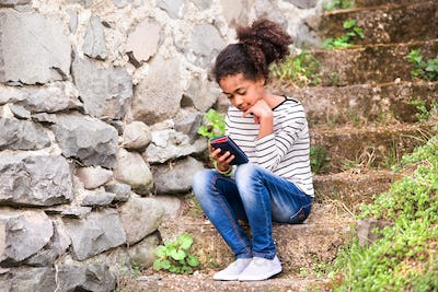 Beautiful african american girl with smart phone, sitting on stairs