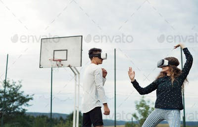Attractive teenagers on playground with VR glasses.