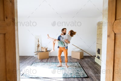 Man carrying woman in his arms, moving in new house.