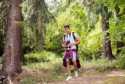 Teenage boy hiking in forest. Summer vacation.