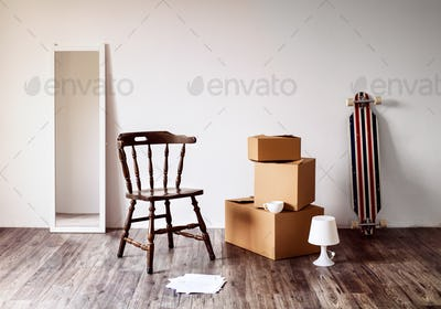 Packed cardboard boxes, mirror, chair and other stuff.