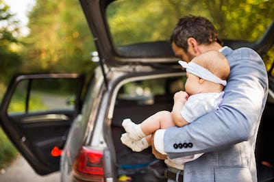 Young father with his little baby girl standing by the car.