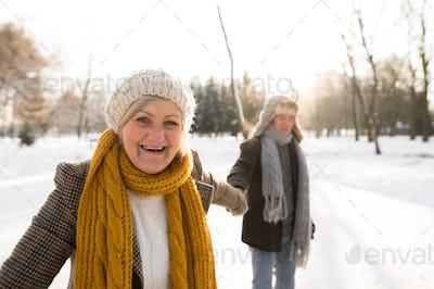 Senior couple in sunny winter nature on a walk.