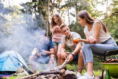 Teenagers camping, cooking meat on bonfire.