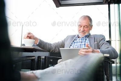 Senior businessman working on tablet in rooftop cafe