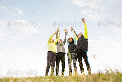 Senior runners outdoors, resting, hands in the air.