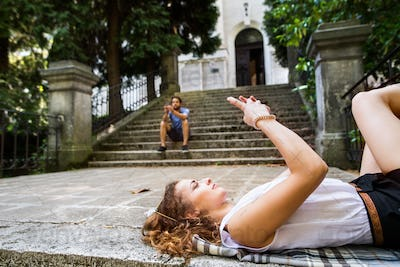 Young couple with smartphones on stairs in town.