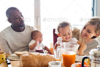 Young interracial family with little children having breakfast.