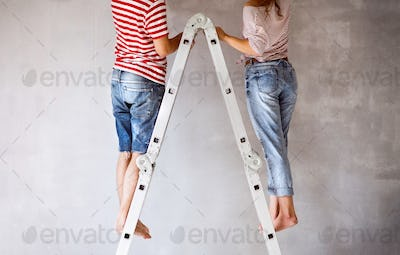 Unrecognizable couple painting walls in their house.