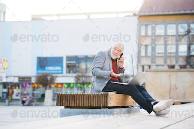 Senior man in town with smart phone, making phone call