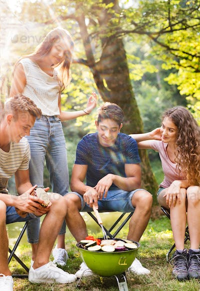 Teenagers camping, cooking vegetables on barbecue grill.
