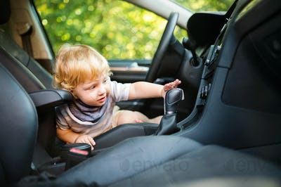 Little boy playing in the car, pretending to drive it.