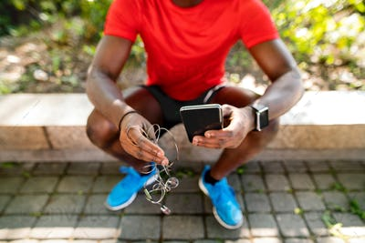 Unrecognizable runner with smart phone, listening music.