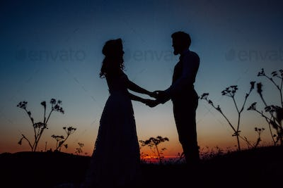 Silouethes of bride and groom on a meadow at night.
