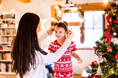 Young mother with daughter at Christmas tree at home.