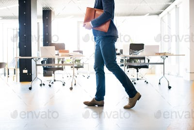 Unrecognizable businessman walking in an office.
