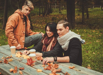 Friends behind wooden table in autumn park