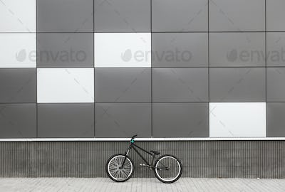 Bicycle leaning on grey wall