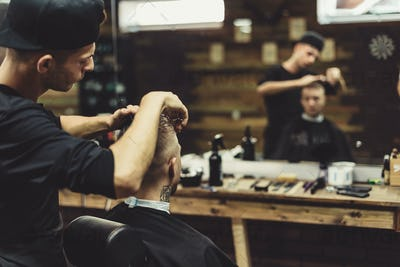Crop barber doing haircut for client