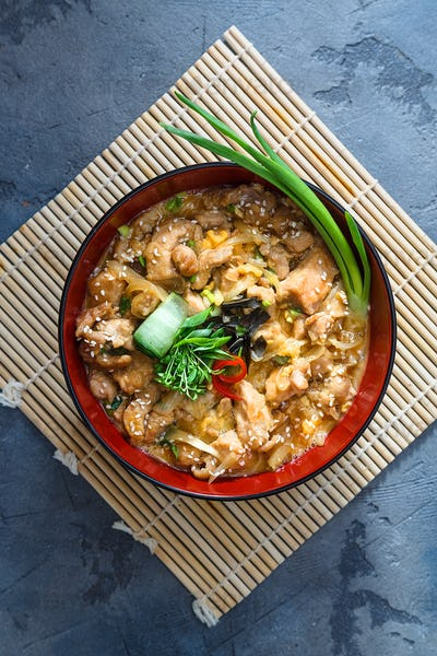 Oyakodon Japanese rice on topped with chicken, egg, onion, and seaweed in ceramic rice bowl.