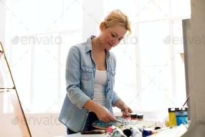 happy woman artist painting at art studio