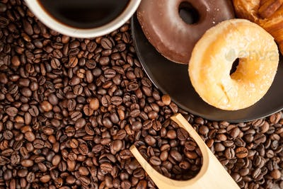 Coffee beans, donut and a cup of coffee