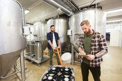 men with beer kegs on loader at craft brewery