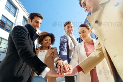 group of happy people holding hands in city
